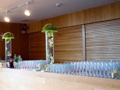 A long bar set with glasses, drinks and table decorations