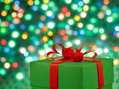 Image of Christmas present with lights in the background
