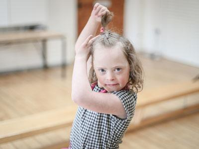 A photo of a young girl with her arms in the air like a flamenco dancer