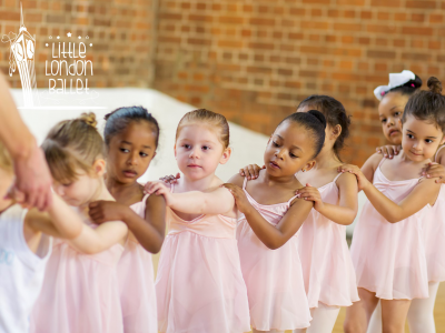 a group of young girls in a line in ballet outfits