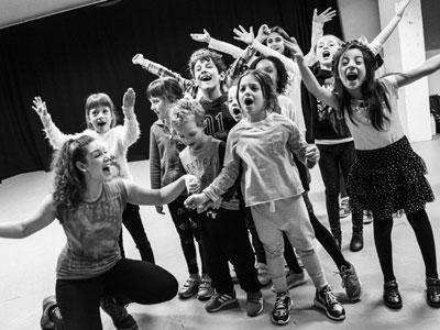 A group of children in a rehearsal studio, happily waving and shouting