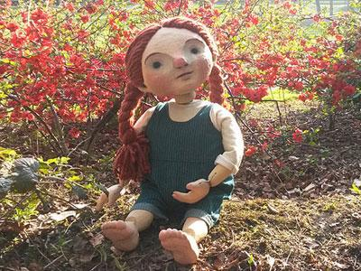 Red-haired Pom sitting in the garden grass in front of red leaves