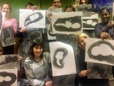 a group of people hold up images that they've made.